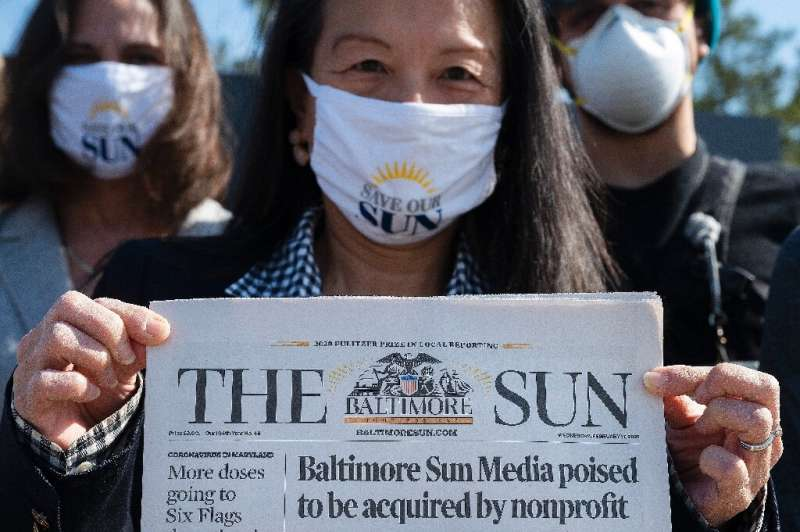 Baltimore Sun reporter Jean Marbella holds up the newspaper's front page that headlined its potential take over by a nonprofit g