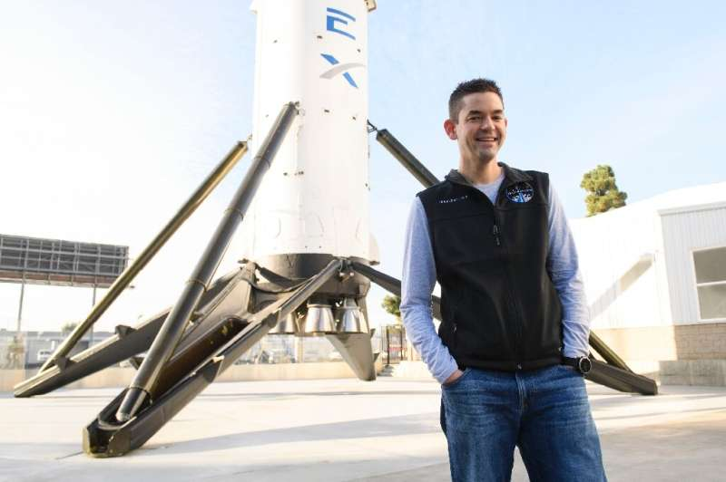 Billionaire Jared Isaacman, who will command the first all-civilian mission into Earth's orbit, stands in front of a Falcon 9 ro