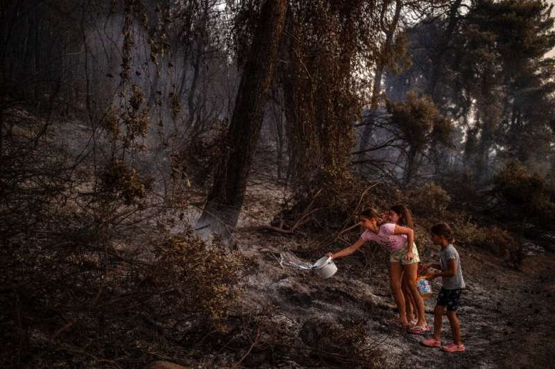 Children pour water on a smouldering fire near the village of Kastri on Evia