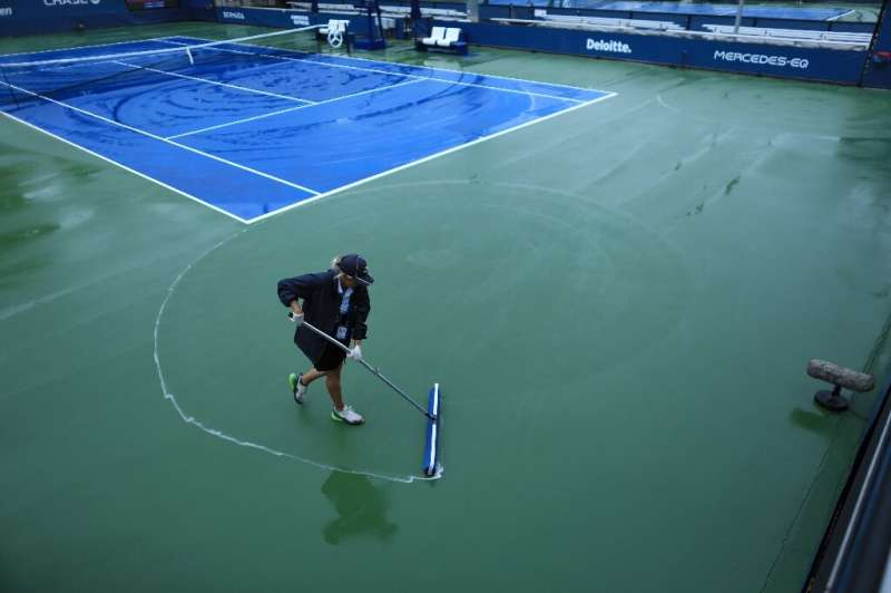 Court staff clean the rain off the courts at the USTA Billie Jean King National Tennis Center in New York, on September 1, 2021
