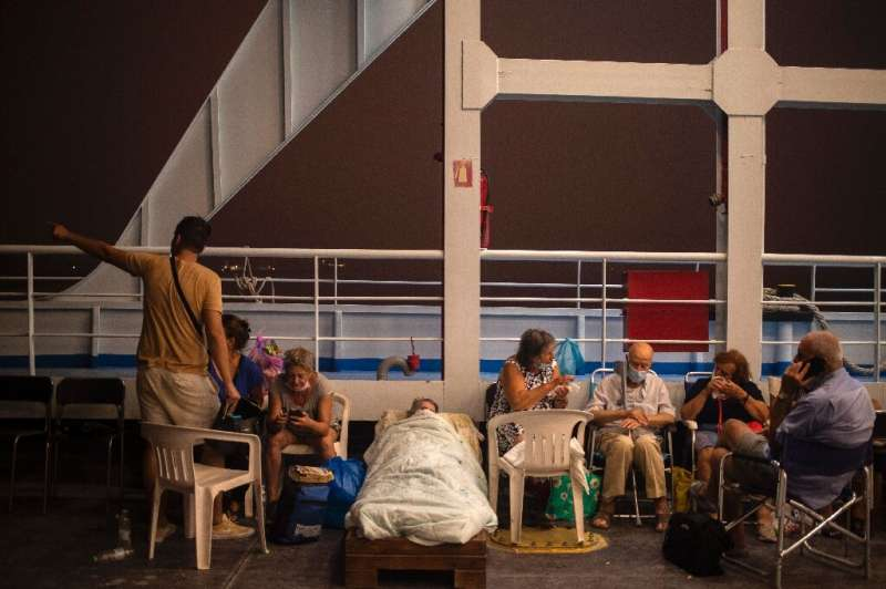 Elderly people take shelter for the night on board a ferry at Pefki, on Evia