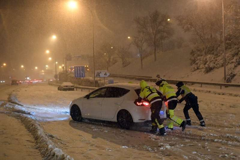 Emergency services workers and soldiers freed 2,500 drivers trapped by the storm, which killed at least three people—these firef