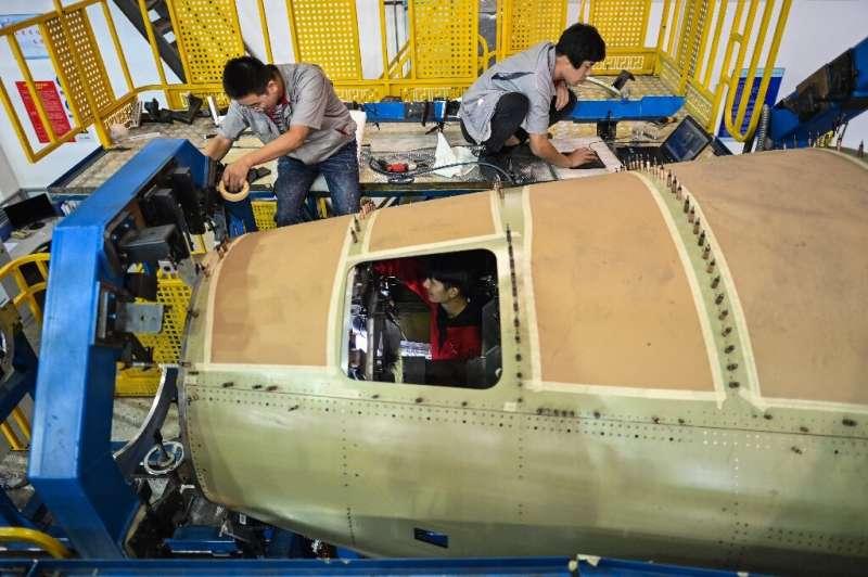Karyawan bekerja di bagian belakang badan pesawat C919