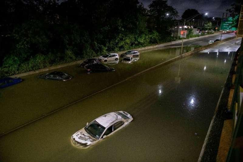 El agua de la inundación rodea a los vehículos tras las fuertes lluvias en una autopista en Brooklyn, Nueva York