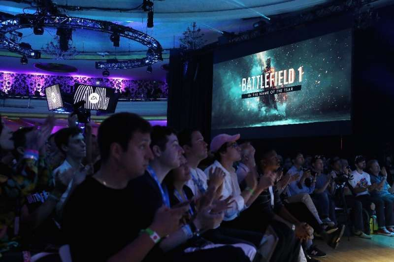 Game enthusiasts and industry personnel watch scenes from 'Battlefield One' during the Electronic Arts EA Play event on June 10,