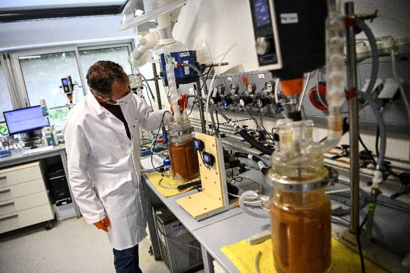 Glass jars containing pulverised electronics are injected with bacteria at a lab in western France by engineers aiming to extrac