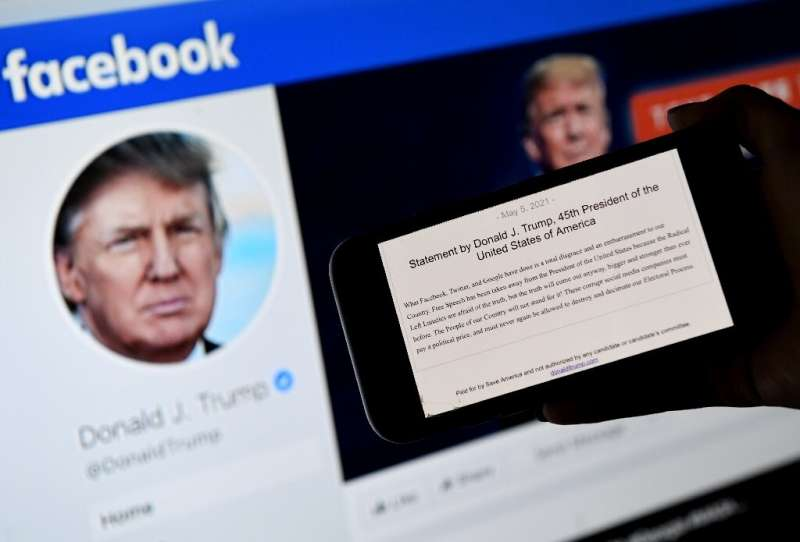 In this file photo illustration, a phone screen displays the statement of former US president Donald Trump on his Facebook page