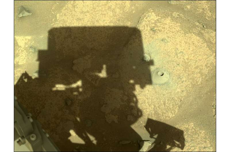 In this image acquired on August 6, 2021 and released by NASA, the shadow of the Perseverance Mars rover is cast next to its fir