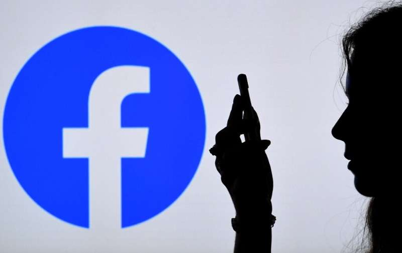 In this photo illustration, a person looks at a smart phone with a Facebook App logo displayed on the background, on August 17,