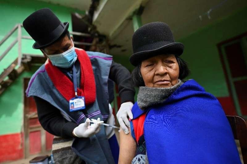 Indigenous nurse of the Misak ethnic group Anselmo Tunubala, 49, inoculates an elderly indigenous woman with a Sinovac vaccine a