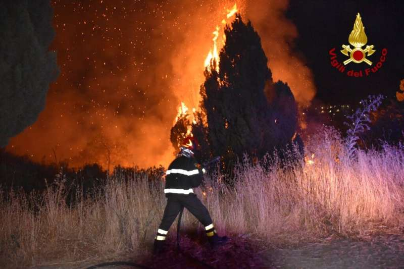 """Italian firefighters, """"Vigili del Fuoco,"""" battle a blaze raging around Palermo, Sicily, that has forced people from th"""