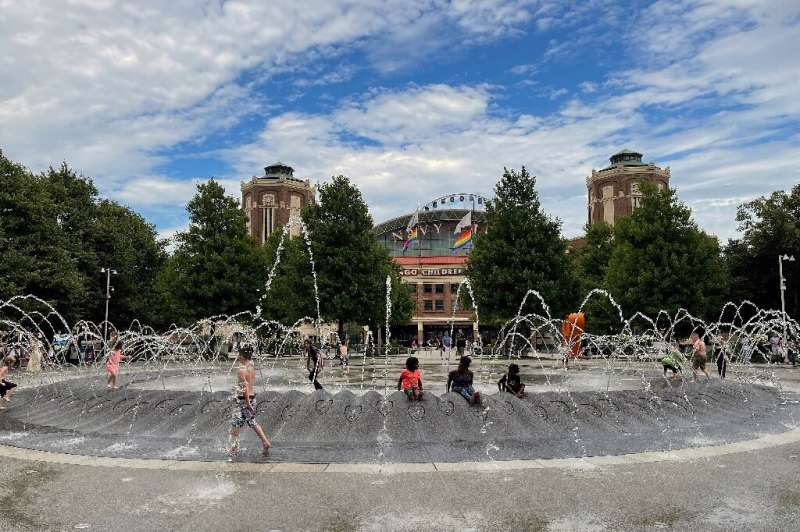 Kids play on a water fountain in downtown Chicago as they try to escape the heat
