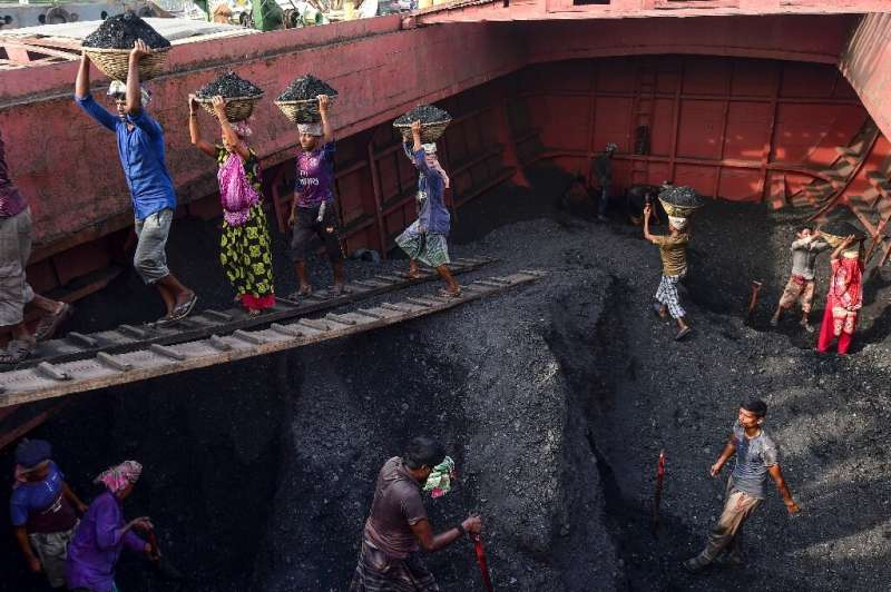 Labourers unload coal from a cargo ship in Gabtoli on the outskirts of Dhaka