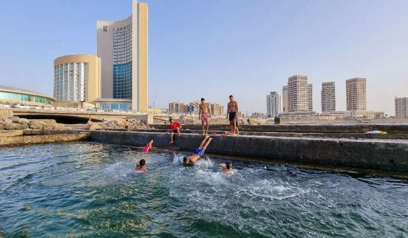 Libyans swim in the Mediterranean at the capital Tripoli's waterfront. Libya's infrastructure has been devastated by a decade of