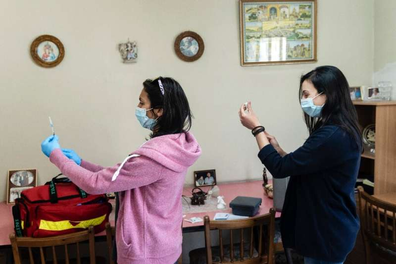 Medics in the Cypriot mountain village of Kyperounta prepare to inoculate a resident with the AstraZeneca vaccine