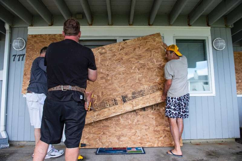 Members of the Edelweiss construction crew worked fast to protect costal homes by barricading their windows and doors with plywo