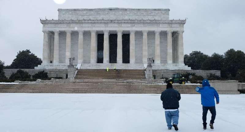 Men are seen outside of the Lincoln Memorial under a blanket of light snow in Washington, DC on February 18, 2021