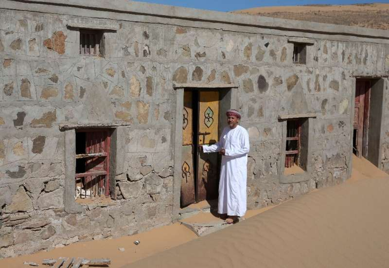 Mohammed al-Ghanbousi, a former inhabitant of Wadi al-Murr, stands next to his abandoned house in the sand-engulfed village