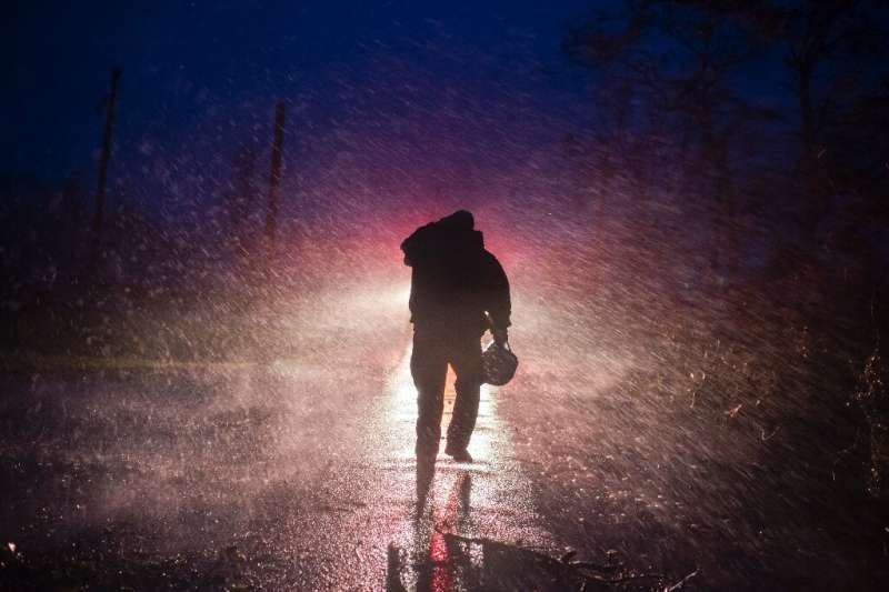Montegut fire chief Toby Henry  walks back to his firetruck after helping cut through trees on the road in Bourg, Louisiana on A