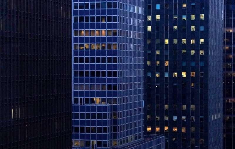 Gedung perkantoran di tengah kota Manhattan yang dulunya terang benderang saat matahari terbenam kini hanya menunjukkan sedikit tanda hunian
