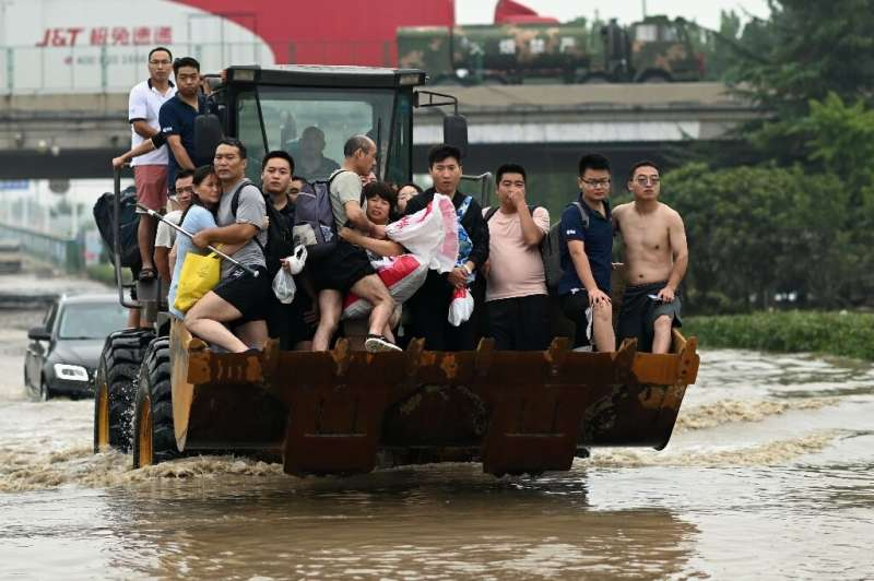 People are carried across a flooded street in the worst-hit city of Zhengzhou, which received a year's worth of rain in just thr