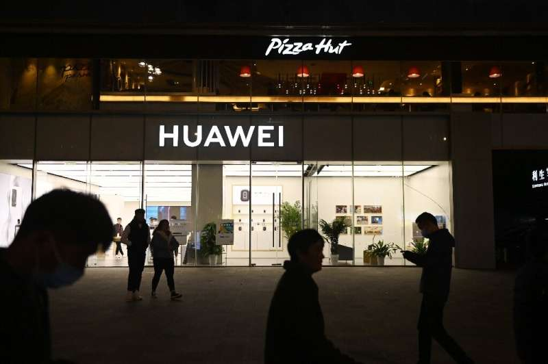 People in Beijing walk in October 2020 past a store of Huawei, the Chinese electronics giant blacklisted by the United States