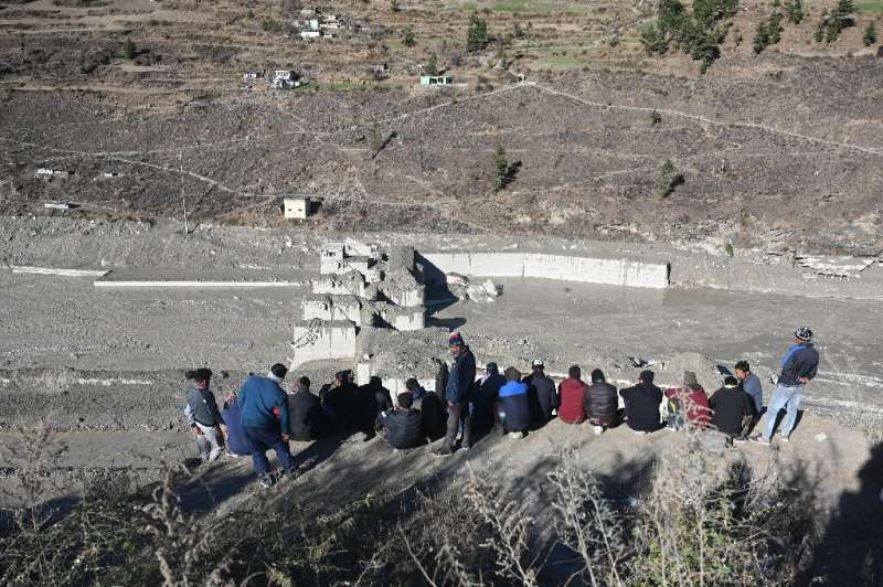 People look at the remains of a dam in Tapovan in the Indian Himalayas that was swept away by a flash flood believed caused by a