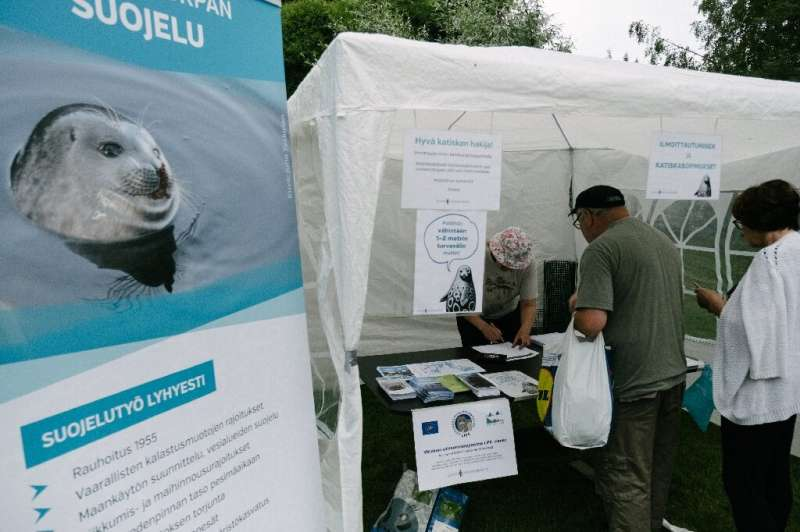 People queue to sign a pledge to stop using fishing nets on Lake Saimaa