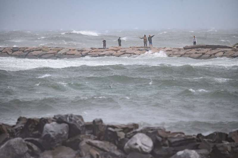 People watch the waves as they stand on a beach as Tropical Storm Henri passes, in Montauk, Long Island on August 22, 2021