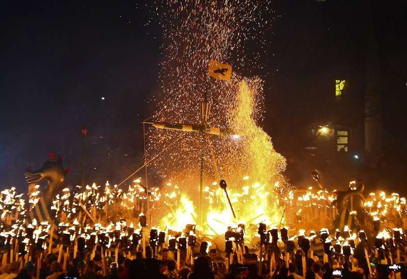 People dressed as Vikings throw flaming torches into their reconstructed longboat at a festival in the Shetland Islands