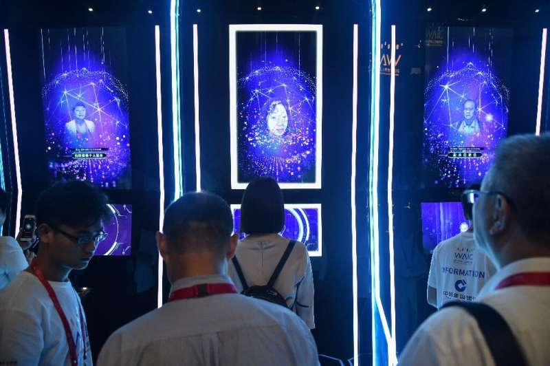 People have their faces scanned as they arrive for the opening ceremony of the World Artificial Intelligence Conference (WAIC) i