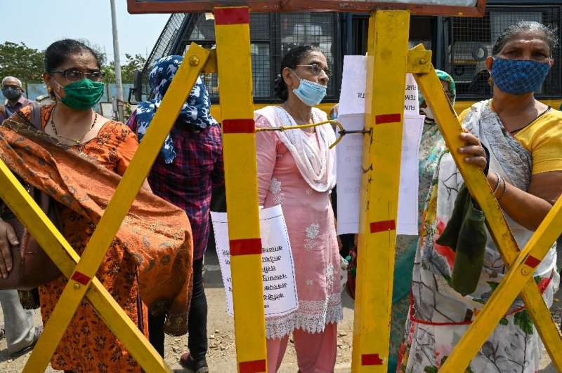 People in Mumbai stand behind a barrier outside a Covid-19 coronavirus vaccination centre after jabs were stopped due to shortag