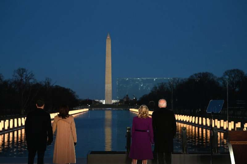 President-elect Joe Biden (R) and incoming First Lady Jill Biden watch as a Covid-19 memorial is lit in Washington, DC