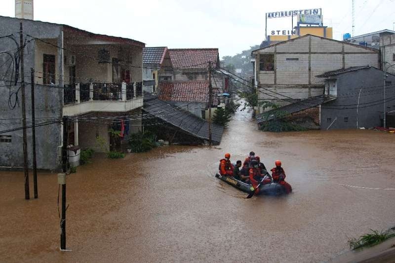 Rescuers paddle a raft through a flooded neighbourhood in Jakarta on Saturday