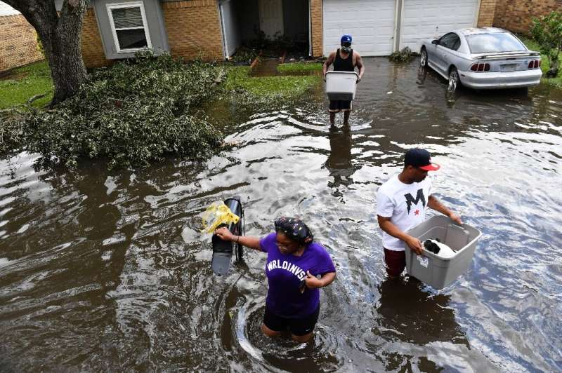 Residents wade out to a high-water truck evacuating people from flooded homes in LaPlace, Louisiana on August 30, 2021
