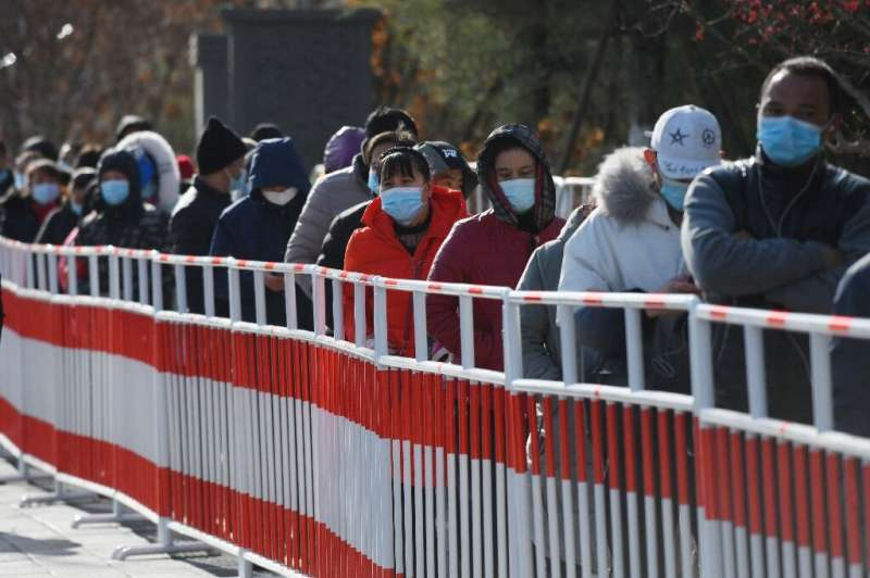 Residents line up to be tested for coronavirus in Beijing on January 11, 2021, after new cases emerged in the province which sur