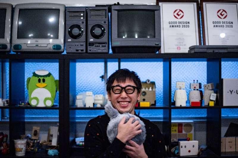 Shunsuke Aoki, CEO of Yukai Engineering, hugs the robotic cushion Qoobo, which has a mechanical tail that wiggles