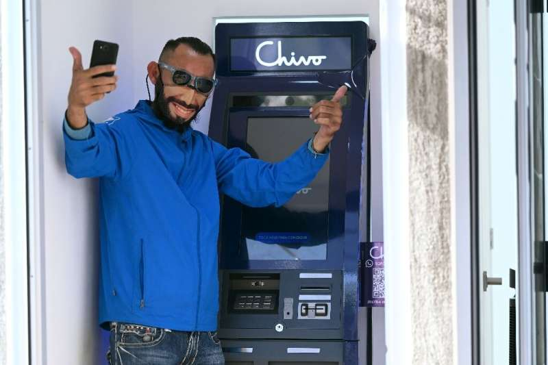 Special ATMs allow people to make bitcoin transactions and draw cash in dollars. This client is wearing a mask resembling Presid