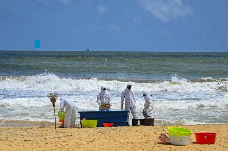Sri Lankan navy personnel remove debris washed ashore from the MV X-Press Pearl ship in Colombo