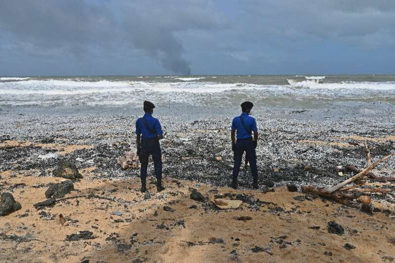 Sri Lankan Navy soldiers stand guard as debris washes ashore from the Singapore-registered container ship MV X-Press Pearl, whic