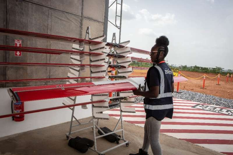 Staff member Georgina Wilson prepares a drone for the delivery of medical supplies at the service base run by operator Zipline i