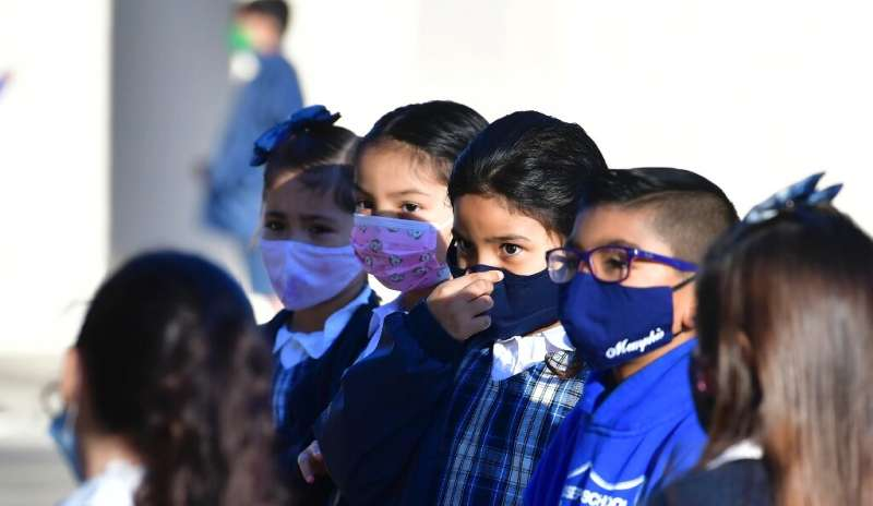 Students wear face masks at a school in the US, where many classrooms remain shuttered due to the pandemic