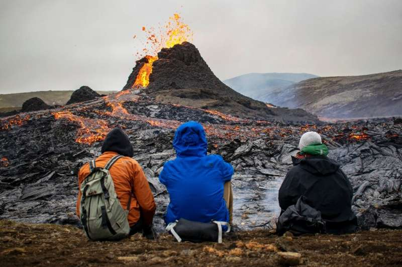 Sunday hikers watch the lava flowing from the erupting Fagradalsfjall volcano