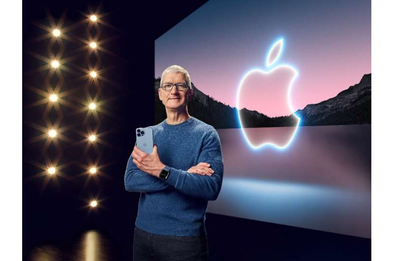 This handout image obtained September 14, 2021 courtesy of Apple Inc. shows Apple CEO Tim Cook with the iPhone 13 Pro Max and Ap