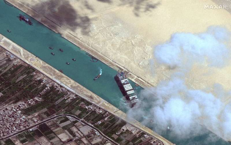 This satellite image released by Maxar Technologies shows the  MV Ever Given container ship and tugboats in the Suez Canal