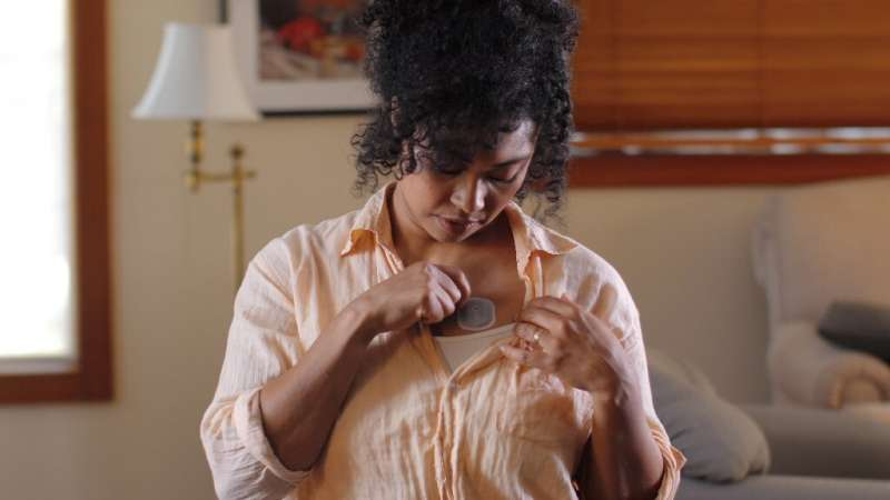 This undated image Courtesy of BioIntelliSense, Inc., shows a woman placing the BioButton, one of the wearables shown in fightin
