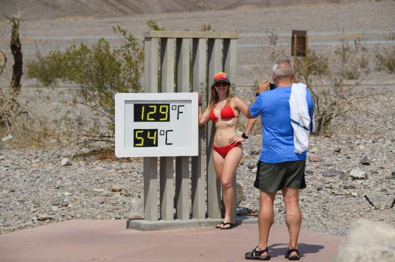 Tourists pose next to a thermometer in California's Death Valley in June. Sweltering conditions have hit much of the Pacific sea