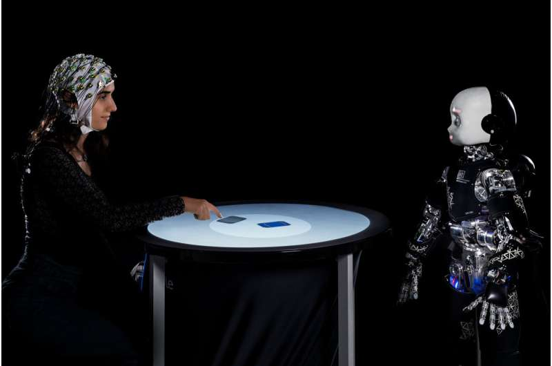 When humans play in competition with a humanoid robot, they delay their decisions when the robot looks at them