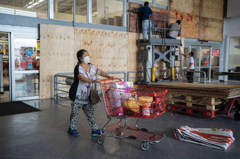 Workers board up windows of a supermarket in Mexico's eastern state of Veracruz to prevent damage from approaching Hurricane Gra