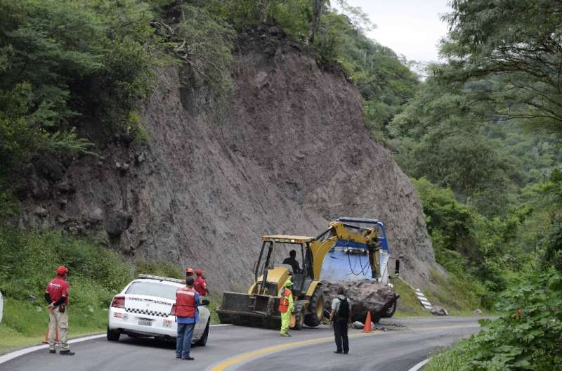Workers remove rocks from a highway after an earthquake near Mexico's Pacific resort of Acapulco